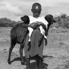 Maasai girl carrying goat